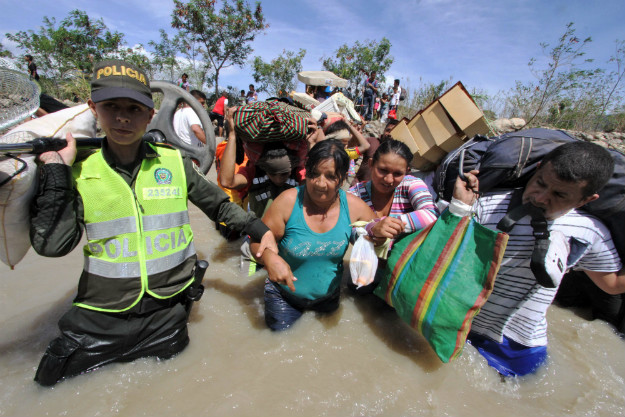 Colombian police help Colombian women carry their belongings as they cross the Tachira border river from Venezuela to Colombia